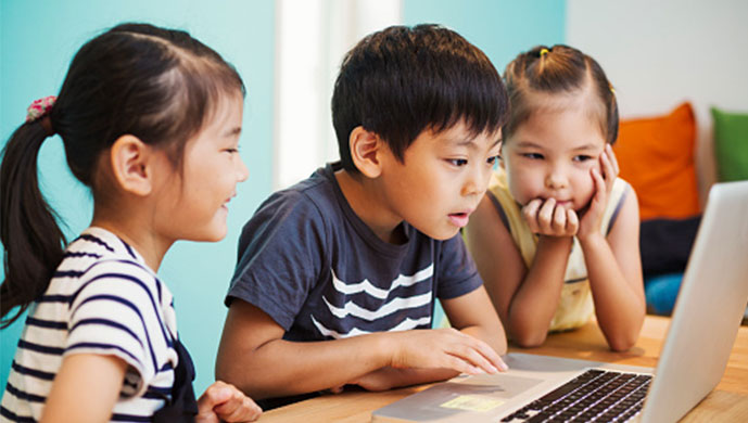 three children watching videos on laptop