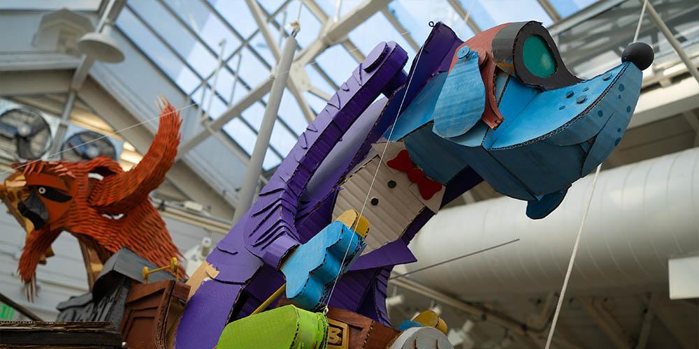 A flying dog sculpture made of cardboard